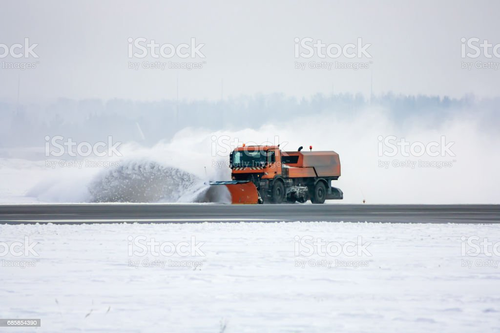 Snow-removal machine cleans the runway at the airport стоковое фото