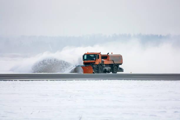 Schneeräummaschine reinigt Landebahn am Flughafen – Foto
