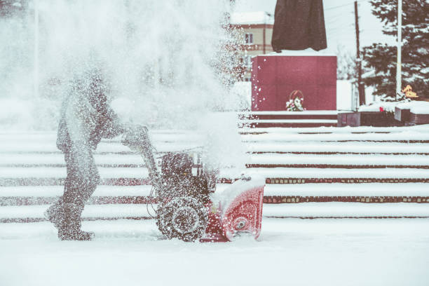 Snow-removal work with a snow blower. Man Removing Snow. heavy precipitation and snow piles. stock photo