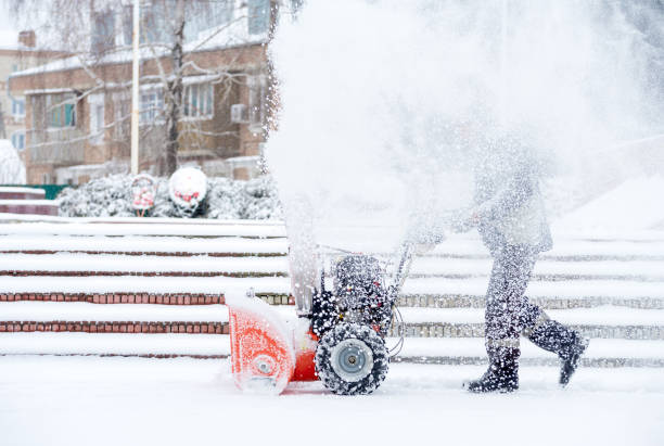 Snow-removal work with a snow blower. Man Removing Snow. heavy precipitation and snow pile stock photo