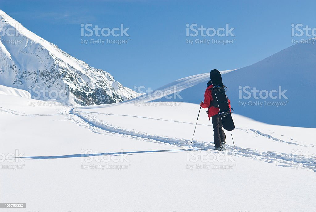 Snowshoe walking with snowboard on the back royalty-free stock photo