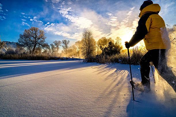snowshoeing at sunset - raquette photos et images de collection