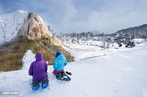 Wyoming, USA - February 21, 2018: Two girls wearing snowshoes sit on a snowy back in front of Orange Spring Mound on the Upper Terraces waiting for a bison to move away from the trees at the next bend in the trail on a guided excursion around Mammoth Hot Springs at Yellowstone National Park during winter