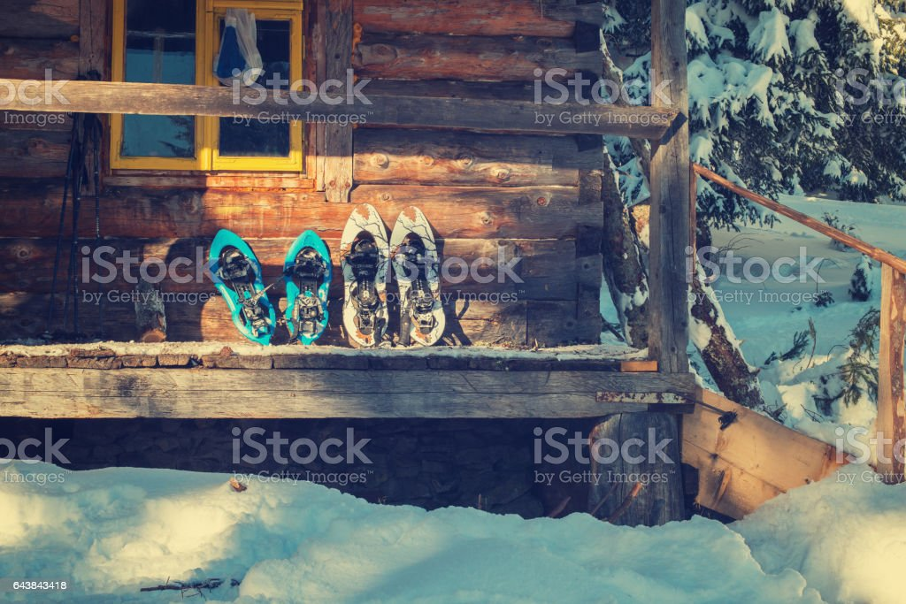 Snowshoes on a porch of old log cabin stock photo