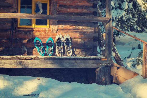 snowshoes on a porch of old log cabin - raquette photos et images de collection