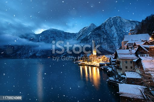Tranquil winter morning in idyllic Austrian village Hallstatt. Snow is falling from the clouds.