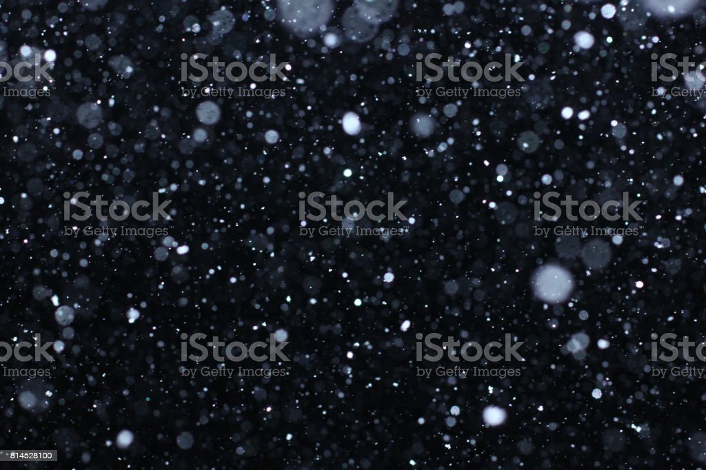 Snowstorm texture. Bokeh lights and Falling snow on a black background stock photo