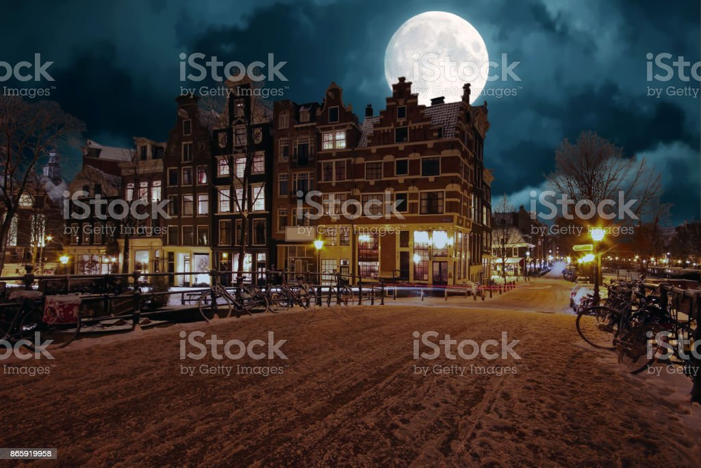Snowy Amsterdam by night in the Netherlands by full moon stock photo