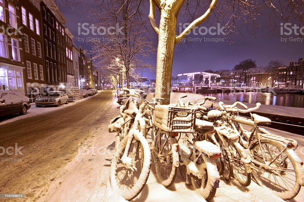 Snowy Amsterdam in wintertime the Netherlands at night stock photo