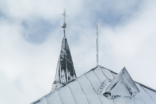 Snowy and cloudy view of chapel at mountains near Zell am See, Austria.
