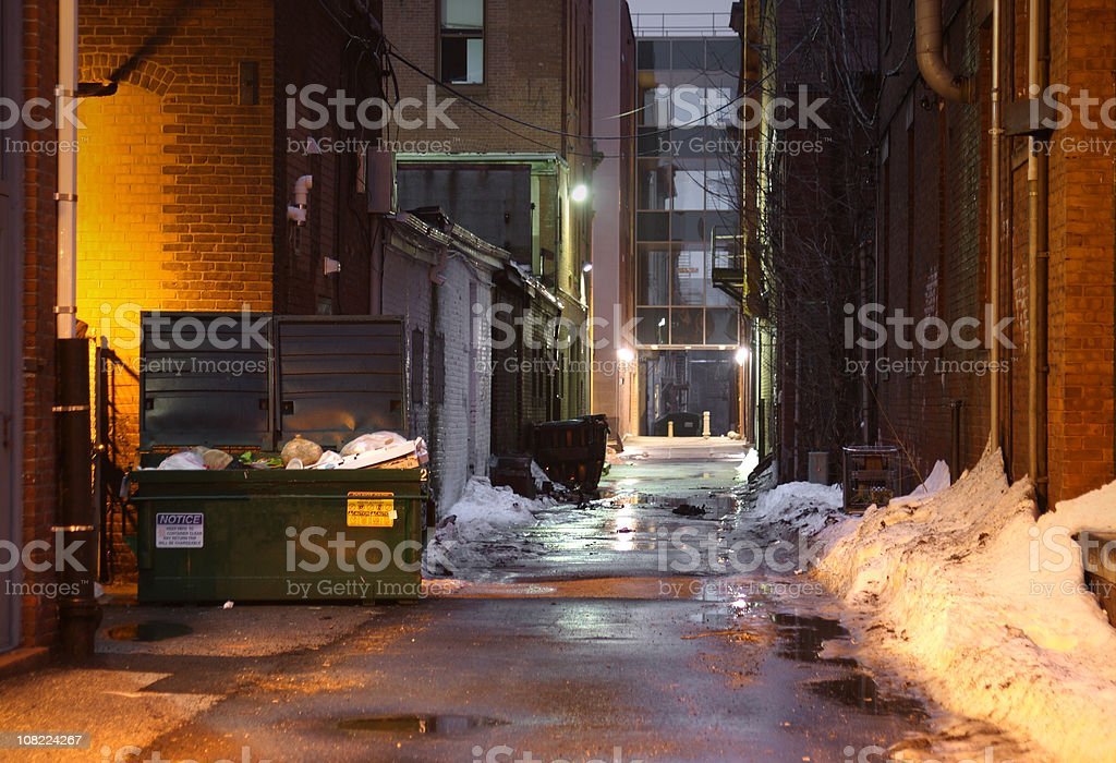 Snowy and Dark, Grunge Alley with Lights Shining at Night stock photo