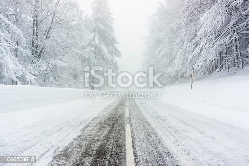 1066508460 istock photo Snowy and icy road in winter through forest 1066508618