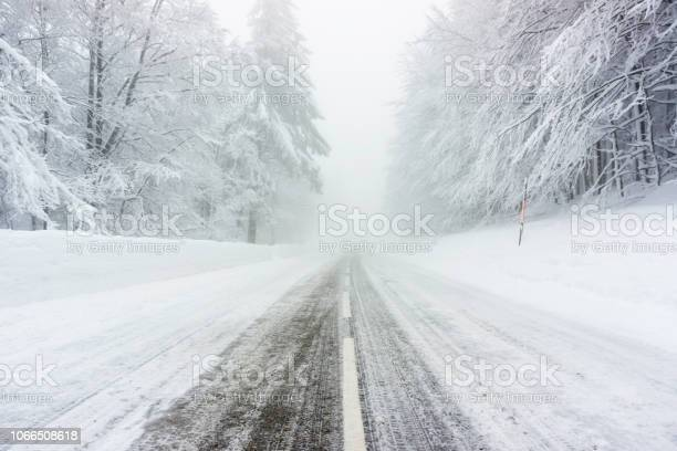 Photo of Snowy and icy road in winter through forest