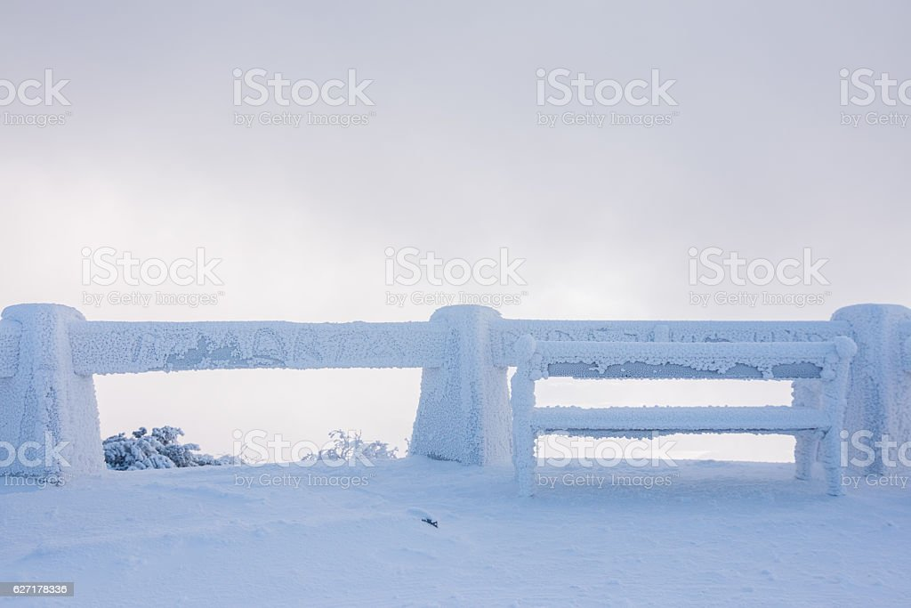 Snowy bench in winter stock photo