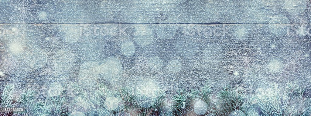 Snowy Christmas Background, Fir Tree Branches And Light Bokeh On Wooden Background, Festive Banner With Copy Space stock photo