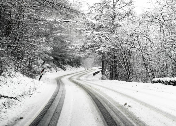Snowy country British road Dangerous driving conditions following overnight snowfall on a winding country road in the Trossachs, Scotland. tire track stock pictures, royalty-free photos & images