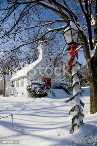 A small white country church located in rural Maryland.  Photo was taken just after a heavy snowfall.  Streetlights in the town are decorated for the holiday.  Deep snow covers the ground.
