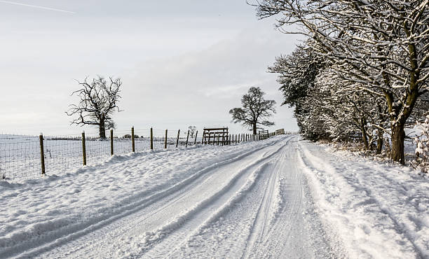 Snowy country lane in Cumbria Snowy country lane in Cumbria, UK on an overcast winter day northwest england stock pictures, royalty-free photos & images
