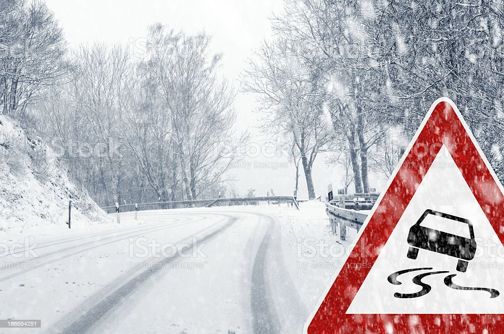 Snowy curvy road with traffic sign stock photo