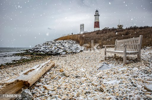 Photograph of Montauk Lighthouse, shore, and bench in foreground with snow coming down