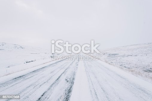657042754 istock photo Snowy empty driving road in the winter Iceland 657042568