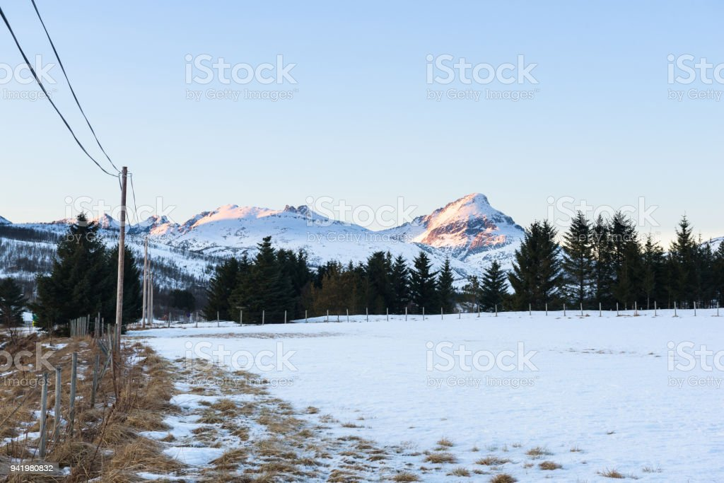 Snowy field surrounded by a fence with mountains in the background bathing in the setting sun stock photo
