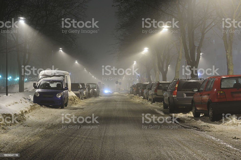 Snowy foggy night street with cars covered by snow stock photo
