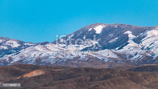 Light snow partially covers the foothills of Boise, Idaho on a clear winter day.