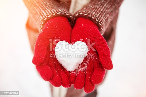 woman holds in her hands a snowy heart
