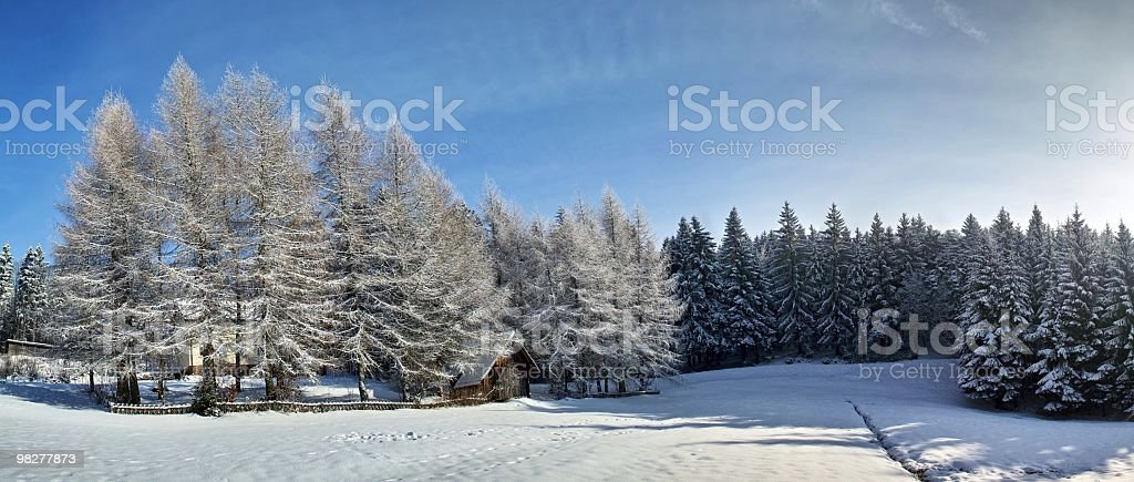 snowy landscape with small cottage and sun royalty-free stock photo