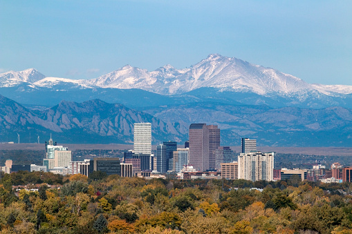 With the snow covered Longs Peak part of the Rocky Mountains and the iconic flatirons of Boulder in the background, Downtown Denver skyscrapers including the iconic
