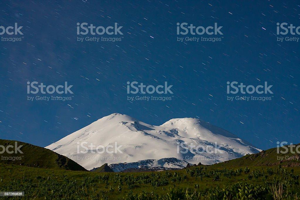 Snowy mountain Elbrus in moonlight and star tracks at night Lizenzfreies stock-foto