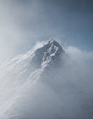 Snowy mountain landscape in cloudy weather