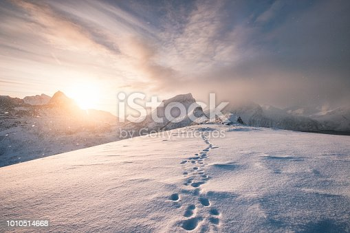 Snowy mountain ridge with footprint in blizzard at sunrise