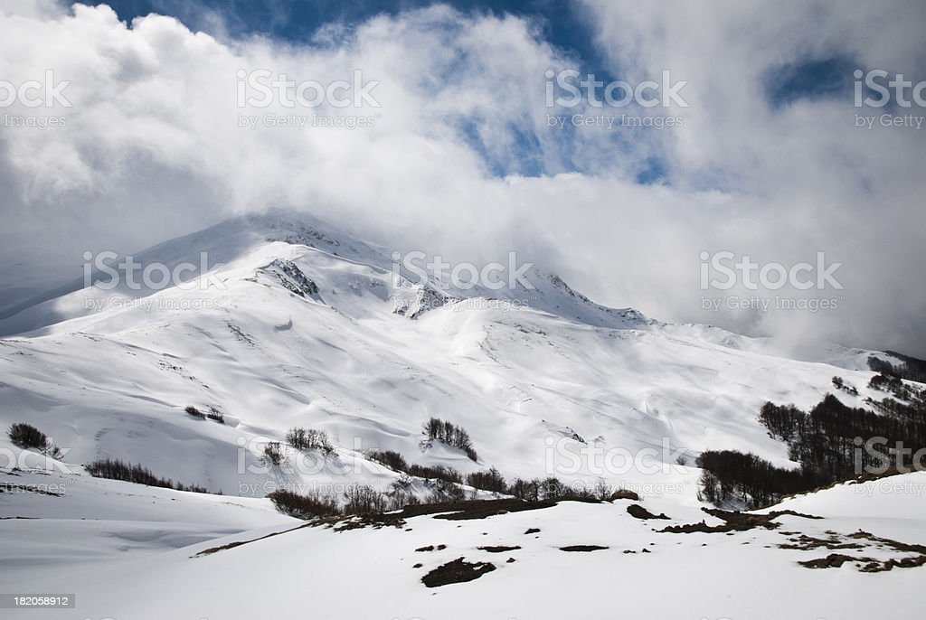 Snowy Mountain Scenery with Dramatic Sky and Clouds stock photo
