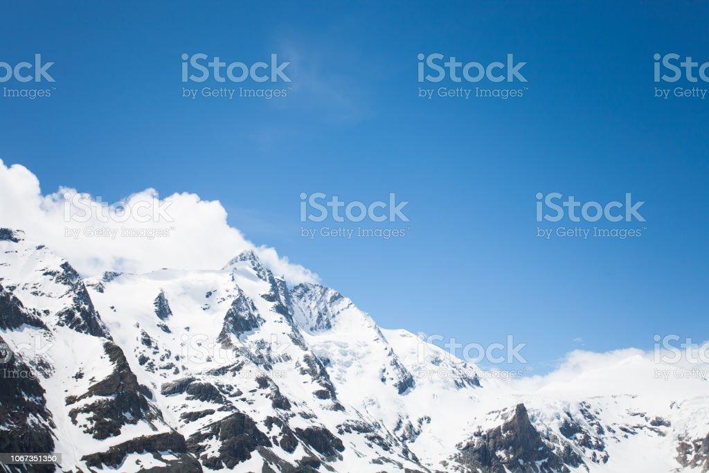 Verschneite Berggipfel (Alpen) in Wolken – Foto