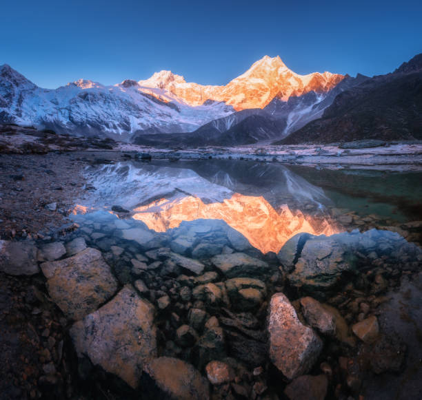 Snowy mountain with illuminated peaks is reflected in beautiful lake at sunrise. Panoramic landscape with lighted rocks, blue sky, pond, stones in water at dawn. Himalayan mountains in Nepal. Nature stock photo