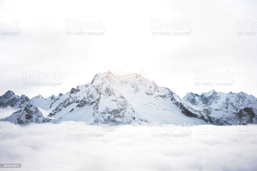 Snowy mountains above the clouds. Great winter massif of rocks royalty-free stock photo