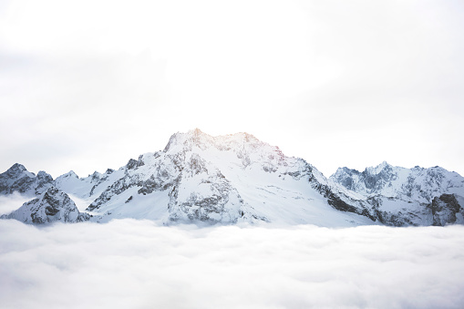Snowy mountains above the clouds. Great winter massif of rocks