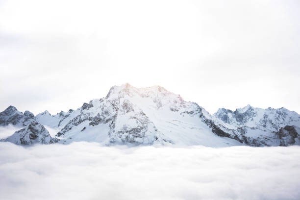 Snowy mountains above the clouds. Great winter massif of rocks stock photo