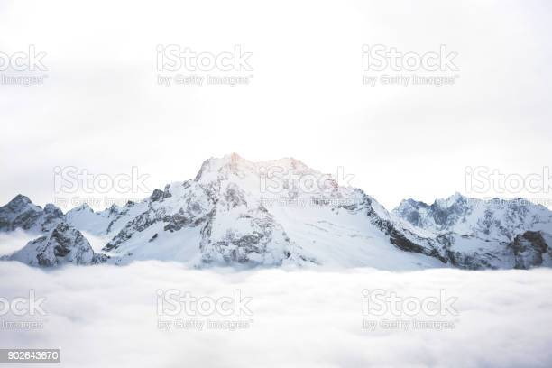 Photo of Snowy mountains above the clouds. Great winter massif of rocks