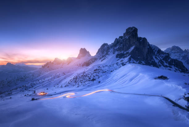 schneebedeckte berge und verschwommene autoscheinwerfer auf der kurvenreichen straße in der nacht im winter. wunderschöne landschaft mit schneebedeckten felsen, haus, bergstraße, blauer sternenhimmel bei sonnenuntergang in dolomiten, italien - alpen stock-fotos und bilder