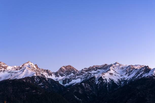 schneebedeckte berge in den österreichischen alpen im winter während der blauen stunde - fiss tirol stock-fotos und bilder