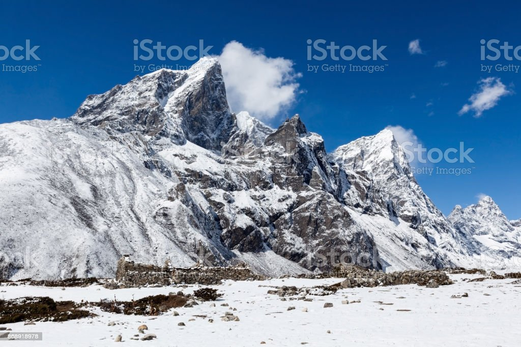 Snowy mountains near Dingboche village on the way to Everest Base Camp. Beautiful landscape of snowy mountains. Bright blue sky and snowy mountains on a sunny day in Himalayas. stock photo