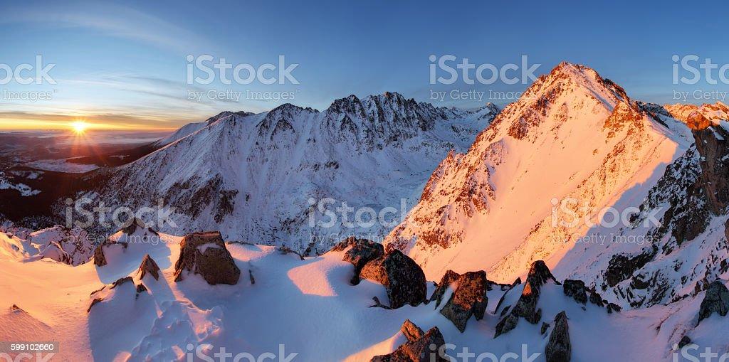 Snowy mountains under orange sunset sky stock photo