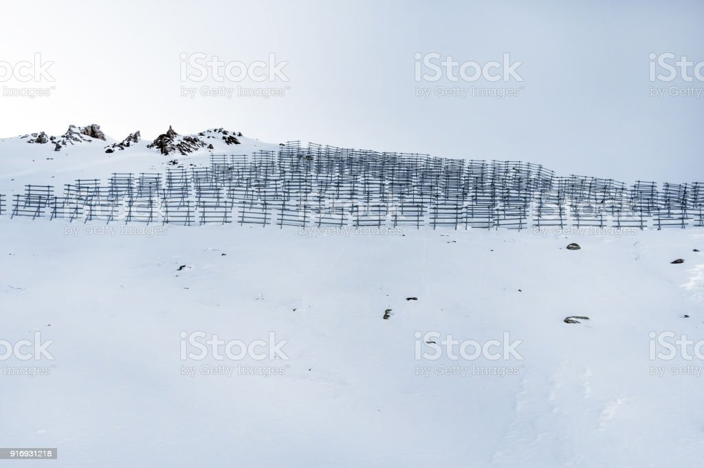 Snowy mountains with barriers in the form of fences stock photo
