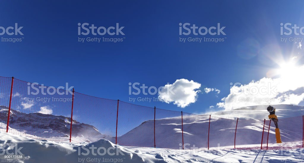 Snowy off-piste ski slope and snow gun on ski resort stock photo