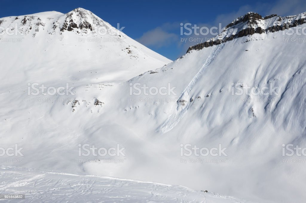 Snowy off-piste slope with traces of skis, snowboards and avalanches stock photo