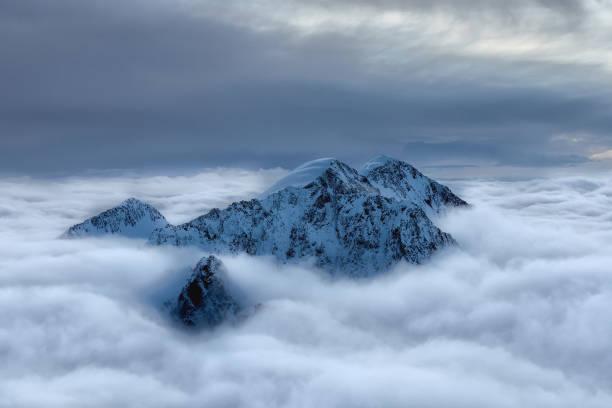 besneeuwde piek boven de wolken - altai nature reserve stockfoto's en -beelden