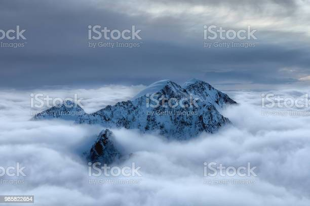 Photo of Snowy peak above the clouds